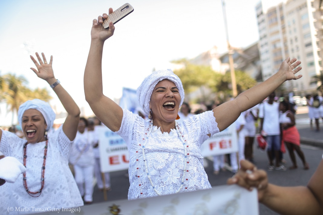 Women in white marching in the street, waving their arms (© Mario Tama/Getty Images)