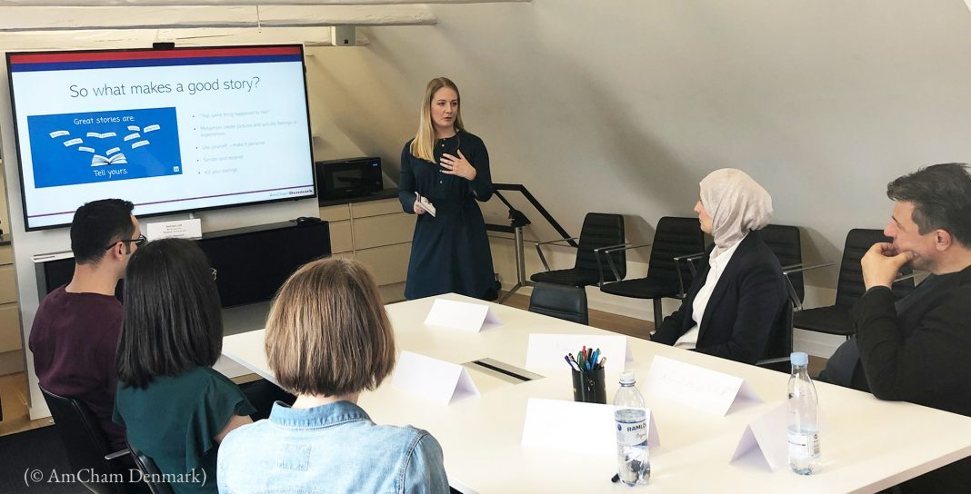 Woman giving presentation to people seated around table (© AmCham Denmark)