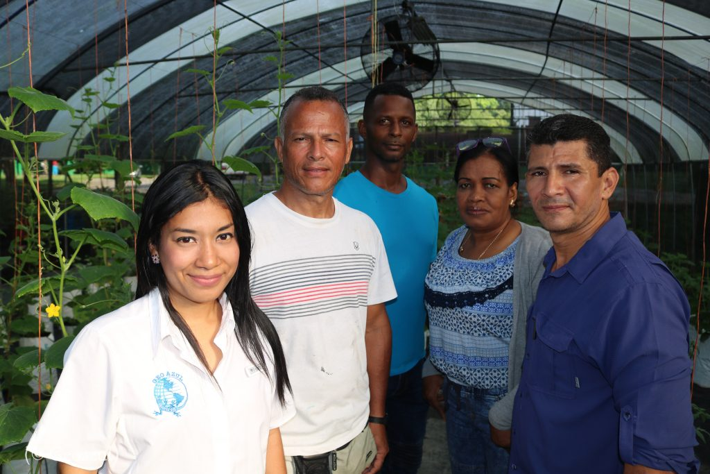 Women and men standing in a greenhouse (© Geoazul)