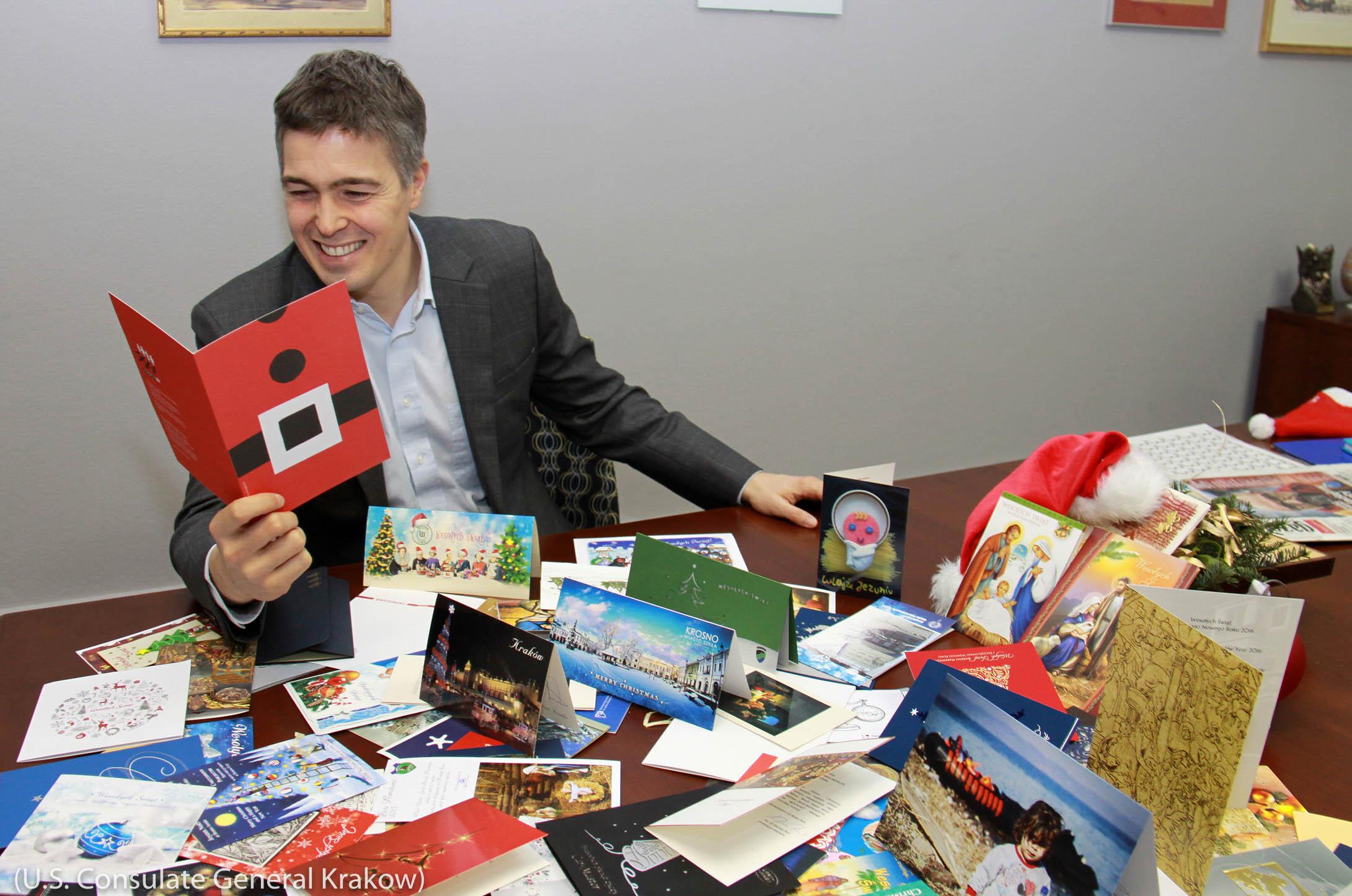 میز پر پڑے ہوئے کرسمس کے کارڈوں کو ایک آدمی پڑھ رہا ہے۔ (U.S. Consulate General Krakow)