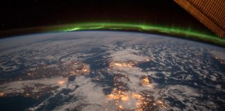 Green aurora stretched over Earth as seen from space (NASA)