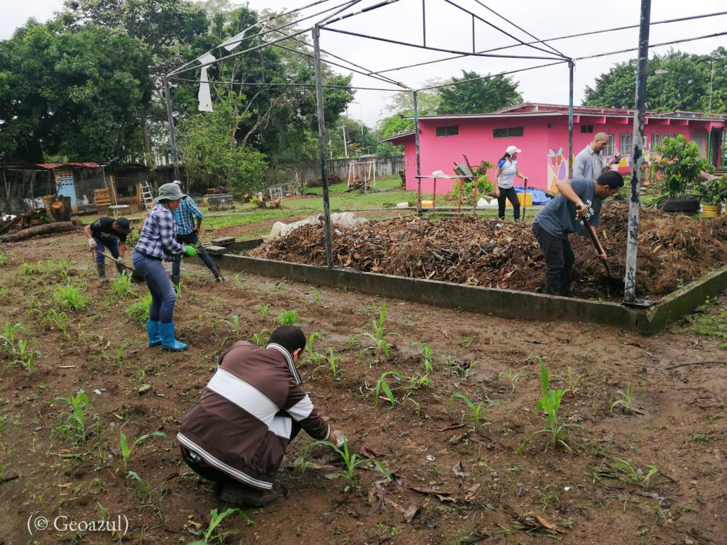 Men and women working the land and mixing compost (© Geoazul)