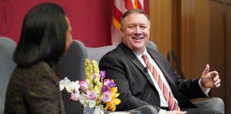 Pompeo (à direita) sentado em uma cadeira conversando com Condoleezza Rice (Departamento de Estado/Ron Przysucha)