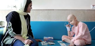 Woman and child with intravenous line playing cards (© Ebrahim Noroozi/AP Images)