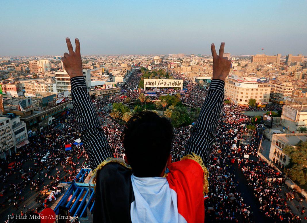 Un homme de dos, les bras levés, tourné vers une foule dans la rue en contrebas (© Hadi Mizban/AP Images)