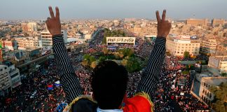 An Iraqi protester flashing the victory sign above crowds of protesters in Tahrir Square (© Hadi Mizban/AP Images)