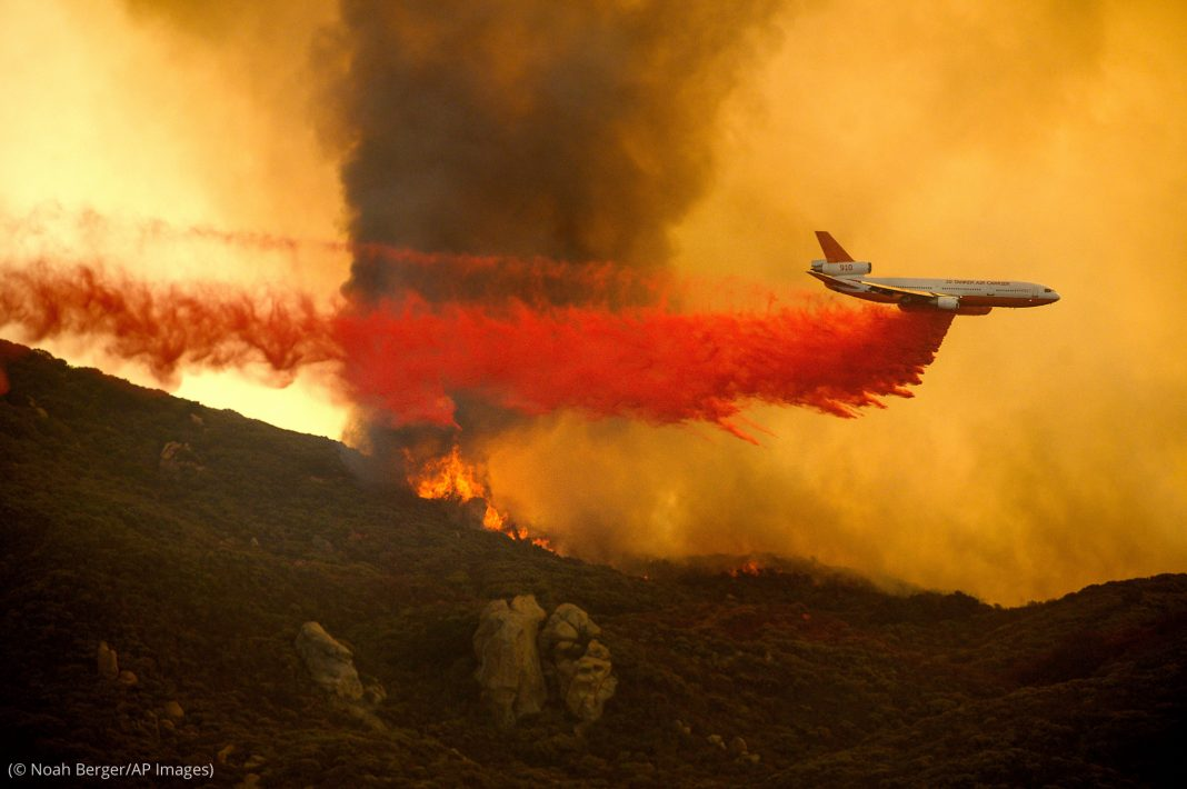 Aircraft dropping red substance on fire (© Noah Berger/AP Images)