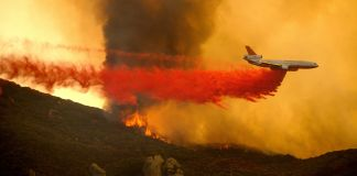 Aircraft dropping retardant on fire (© Noah Berger/AP Images)