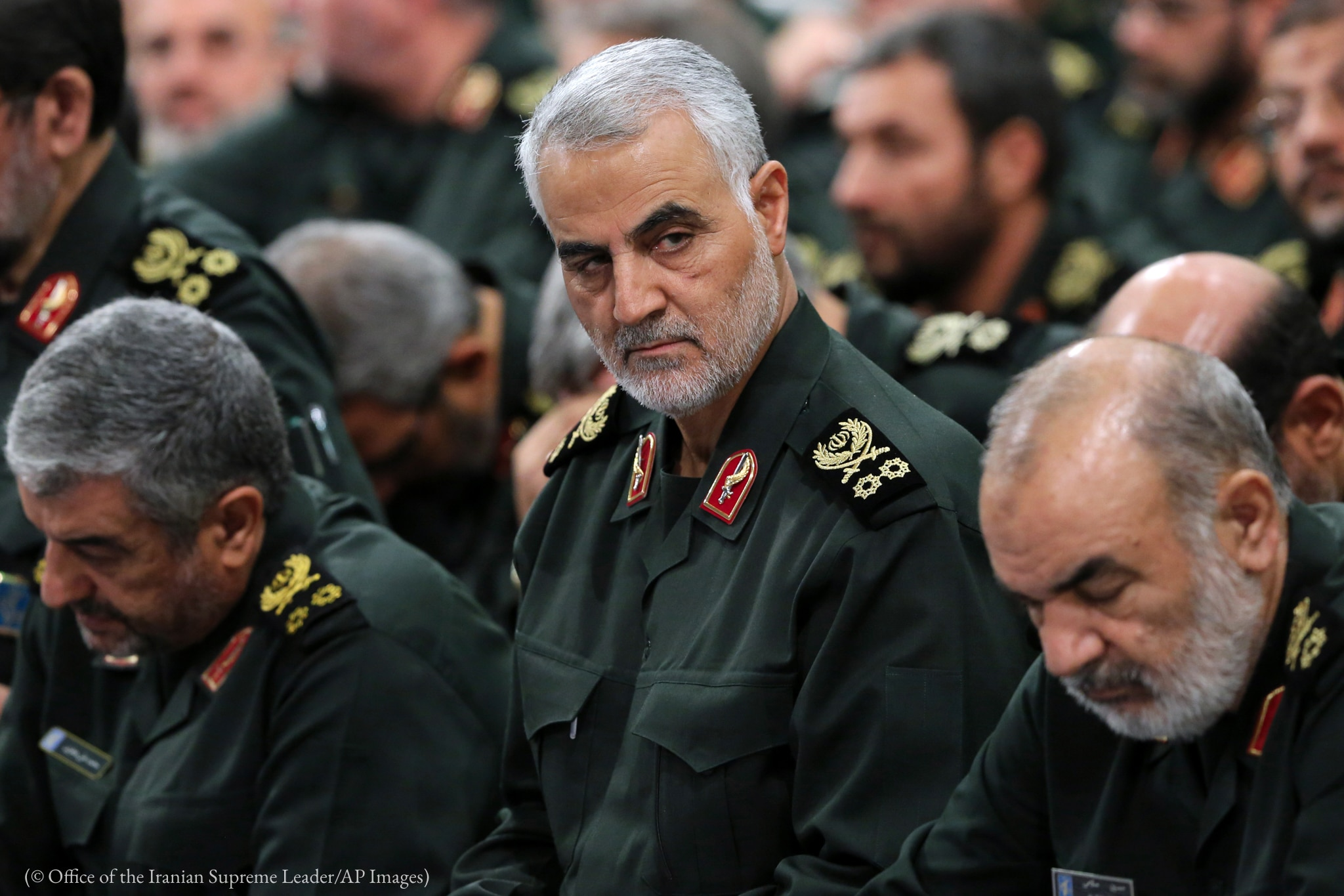 Qassem Soleimani surrounded by people in uniform (© Office of the Iranian Supreme Leader/AP Images)