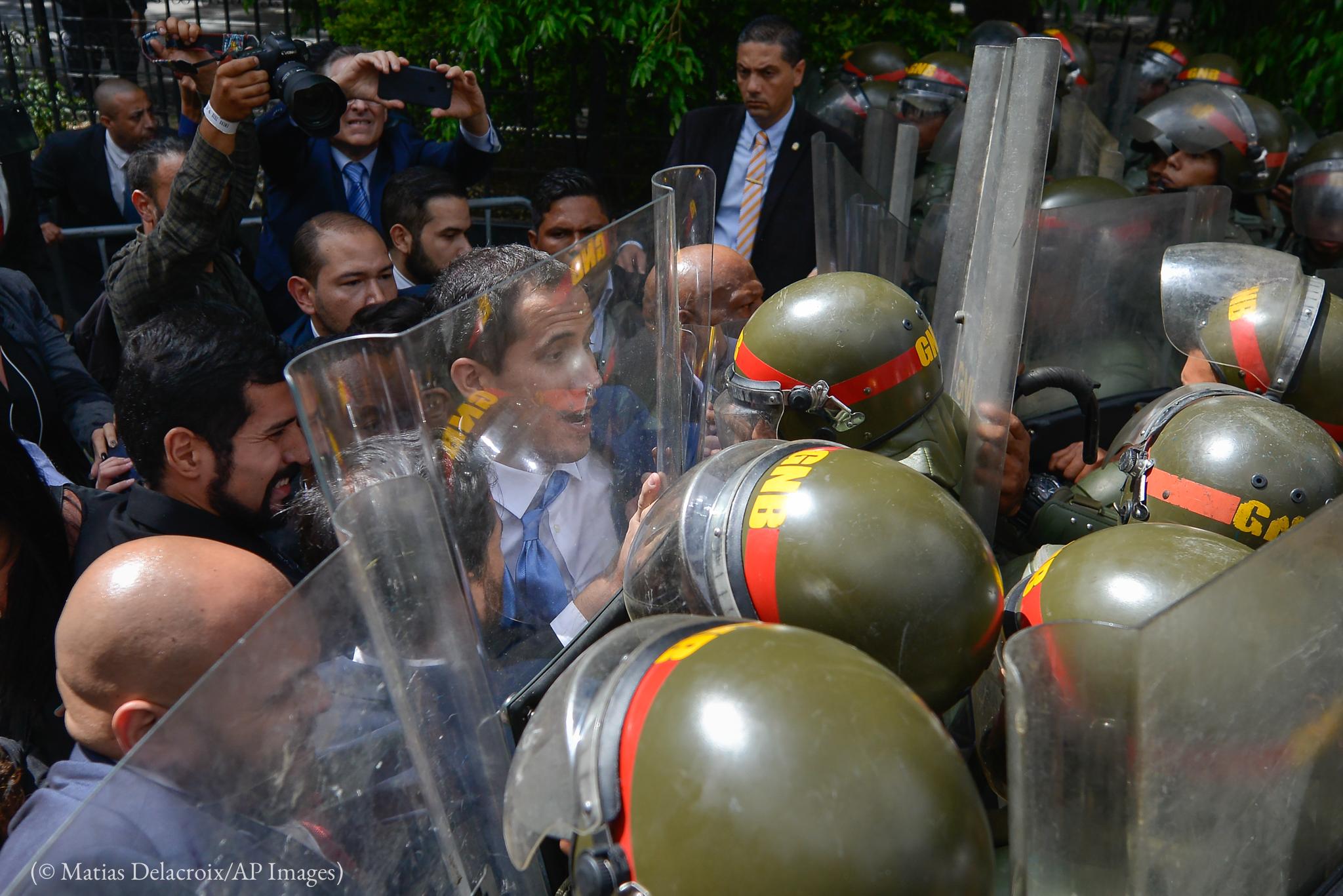 Un homme en costume-cravate, dans une foule, bloqué devant un groupe de policiers en équipement de protection (© Matias Delacroix/AP Images)