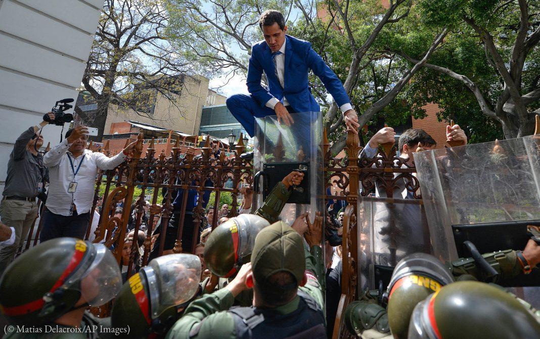 Un homme en costume-cravate en train d'escalader une grille (© Matias Delacroix/AP Images)