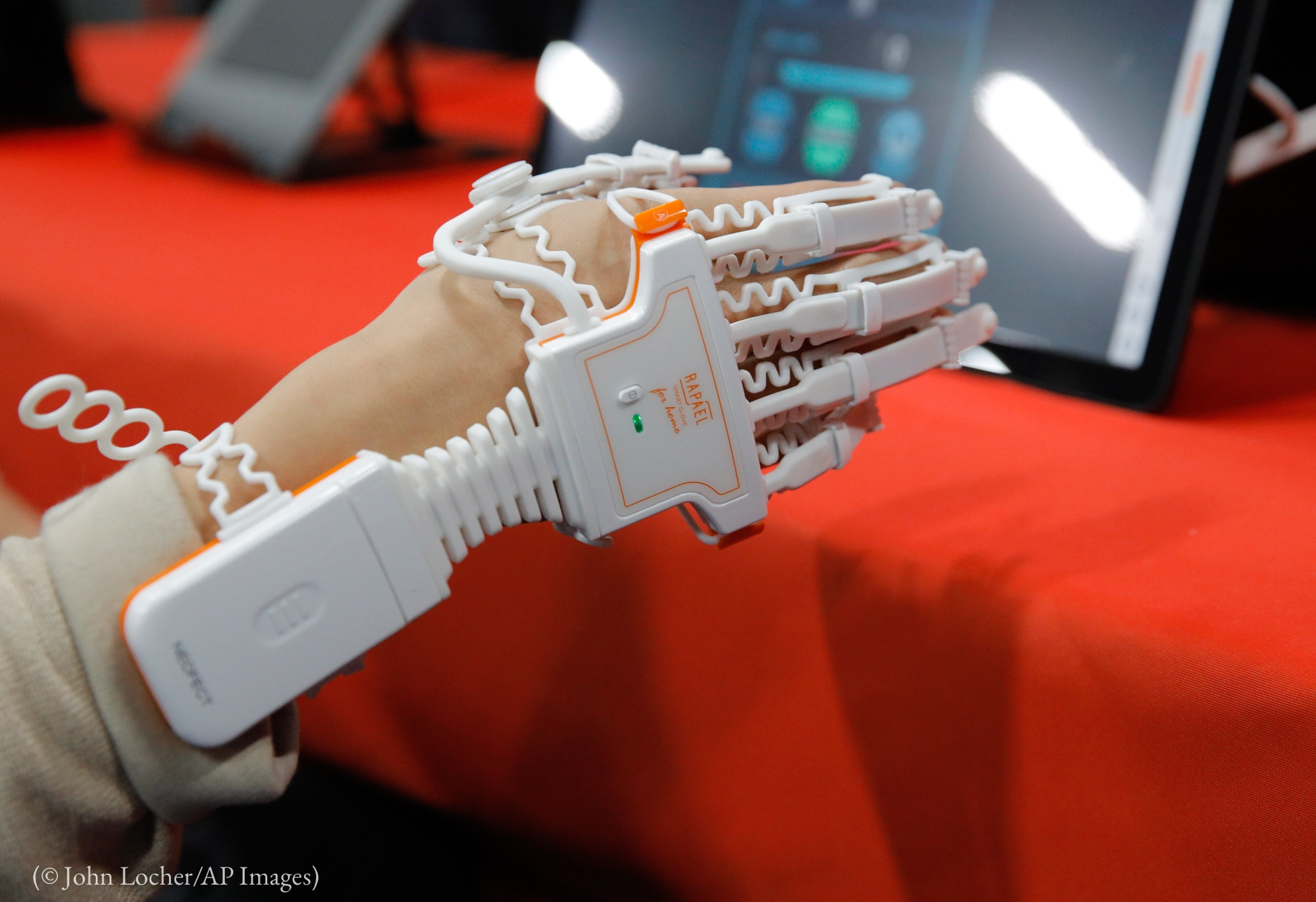 Hand with technology covering it (© John Locher/AP Images)
