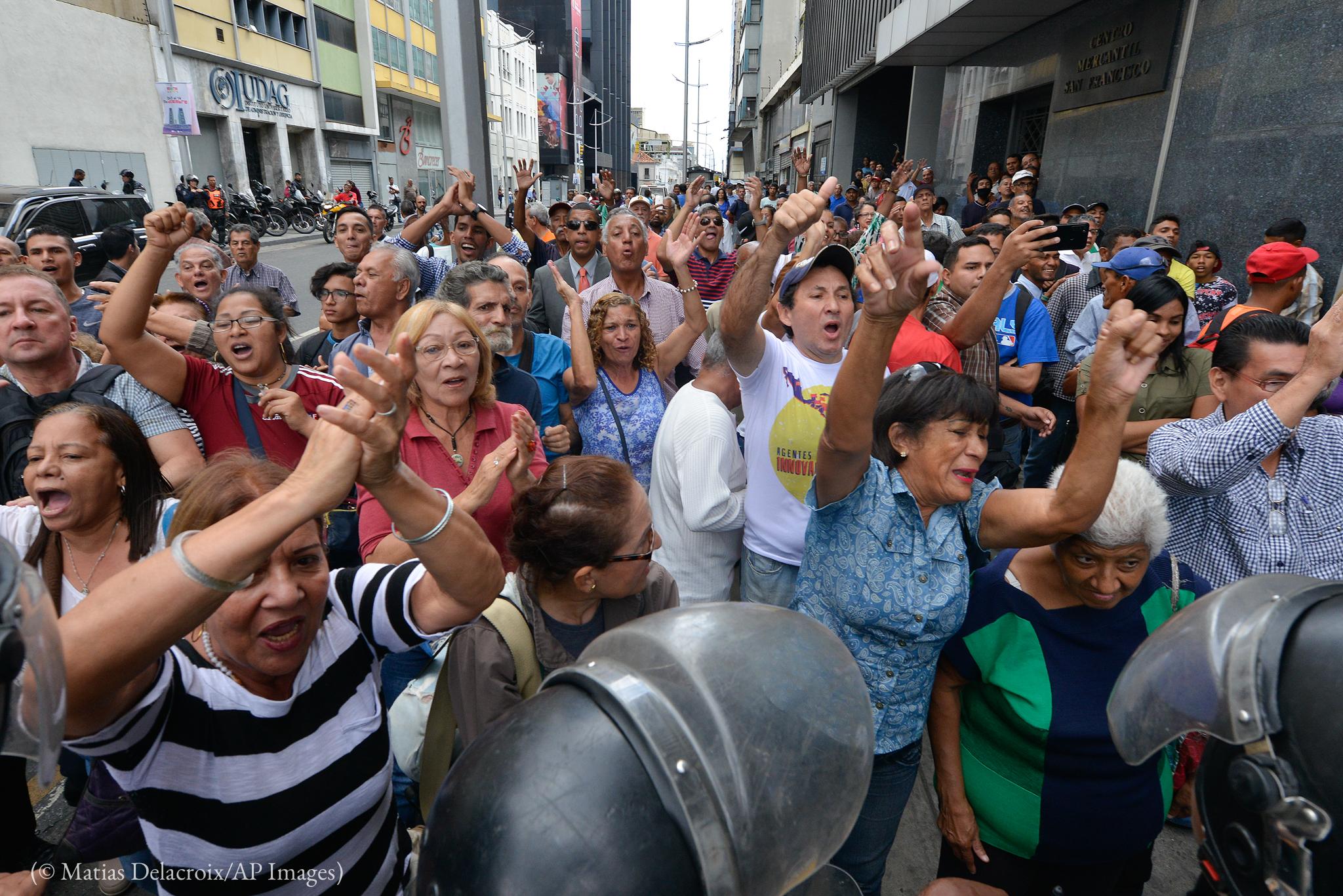 Des gens debout dans la rue, ovationnant M. Guaido (© Matias Delacroix/AP Images)