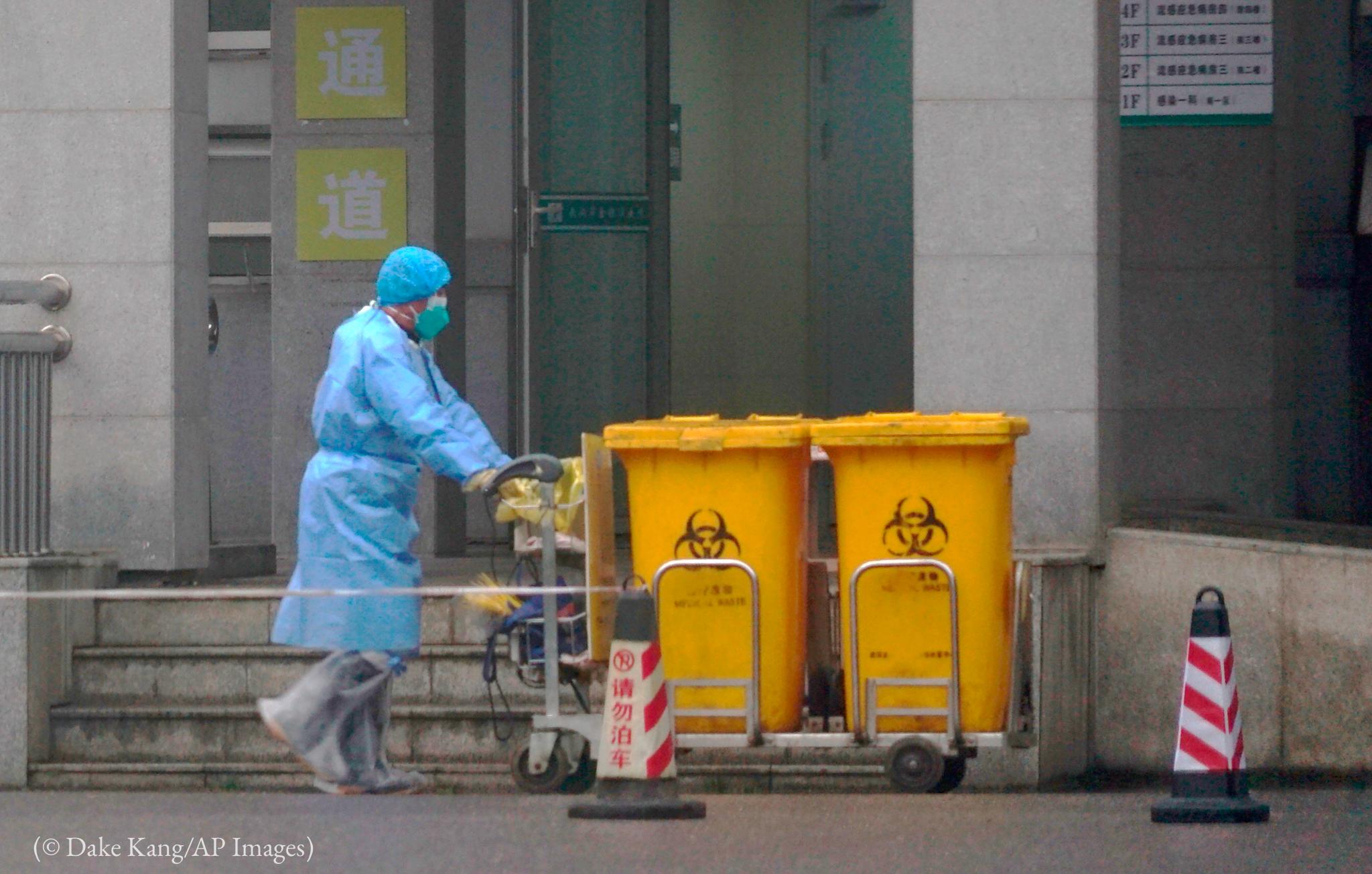 Une personne portant une combinaison de protection médicale poussant deux poubelles devant un bâtiment (© Dake Kang/AP Images)