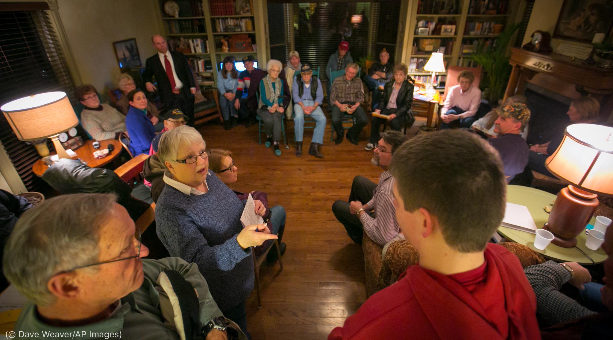 İnsanlar sandalyede oturarak ve ayakta durarak bir konuda tartışıyorlar (© Dave Weaver/AP Images)