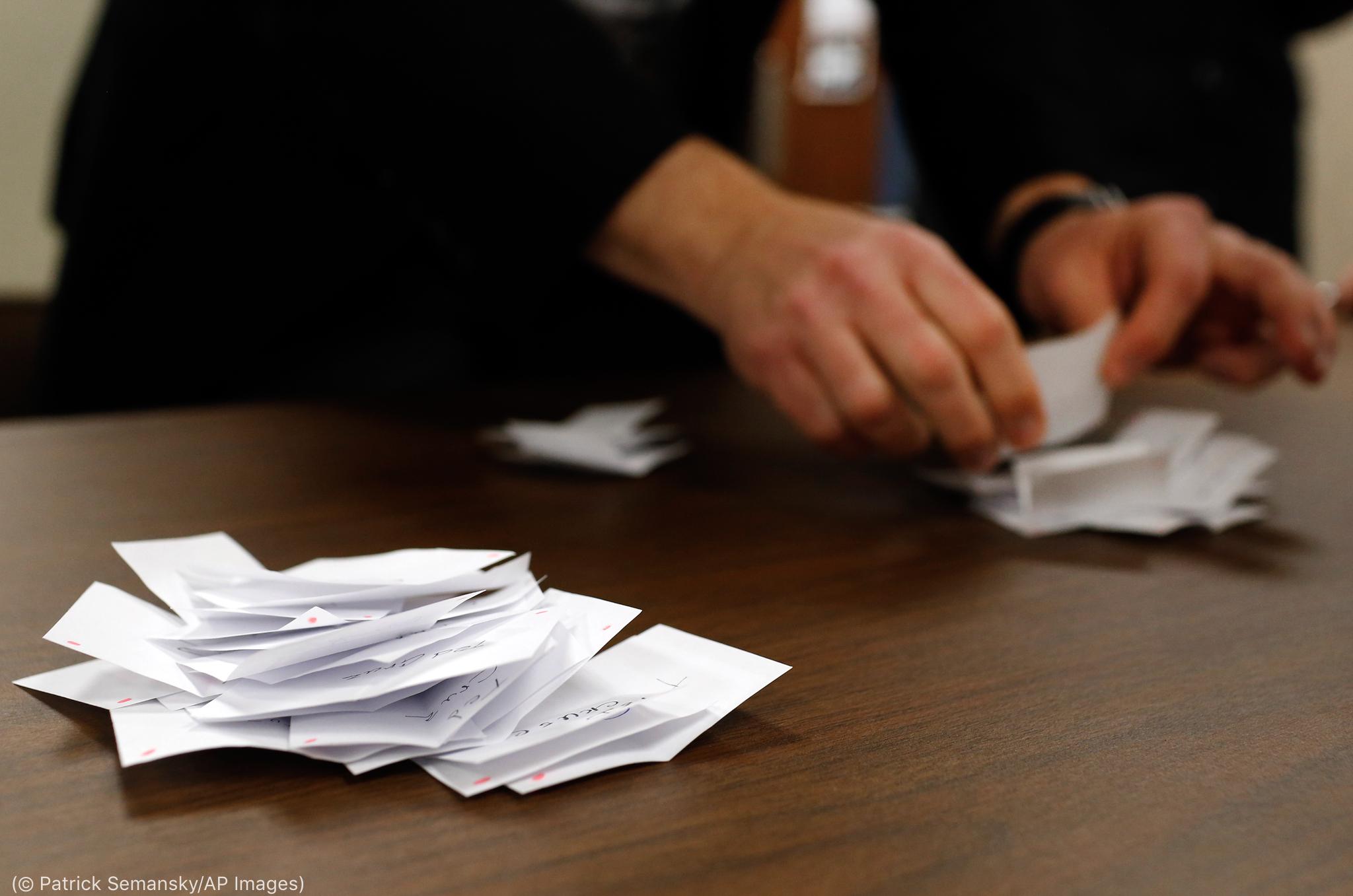 Masada kağıt parçalarını sayan bir adamın elleri (© Patrick Semansky/AP Images)