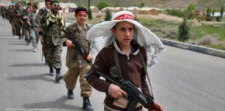 کم عمر فوجی سپاہی مارچ کرتے ہوئے۔ (© Ebrahim Noroozi/AP Images)