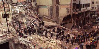 人们头戴安全帽站在被损坏的建筑瓦砾前。 (© Alejandro Pagni/AP Images)