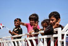 Quatre enfants souriant, agitant des drapeaux (© Muhammet Kasim/Anadolu Agency/Getty Images)