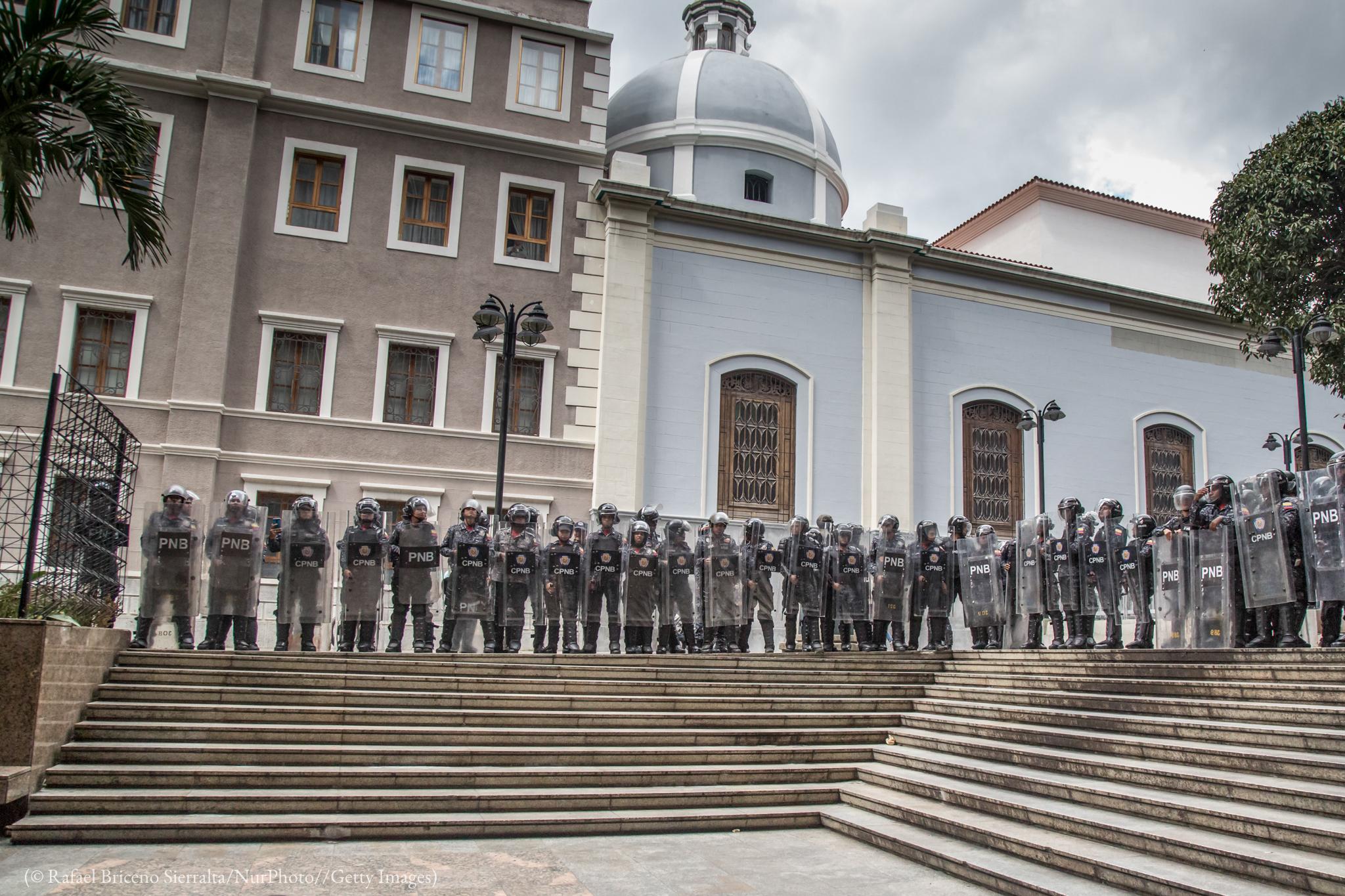 Des personnes en uniforme, équipées de casques et de bouclier, alignées en haut d'un escalier devant un bâtiment (© Rafael Briceno Sierralta/NurPhoto/Getty Images)