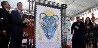 Un groupe de personnes présentant une version géante d'un timbre sur lequel figure un rat (© Xin Huashe/Xinhua/Getty Images)