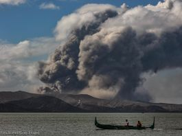 Fishing boat on water in front of erupting volcano (© Ezra Acayan/Getty Images)