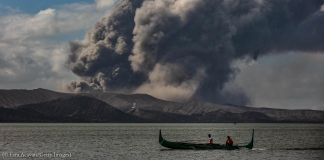 Fishing boat on water in front of erupting volcano (©