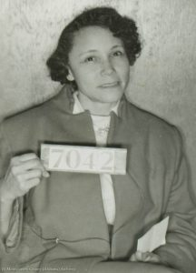 Woman holding sign printed with number (© Montgomery County [Alabama] Archives)