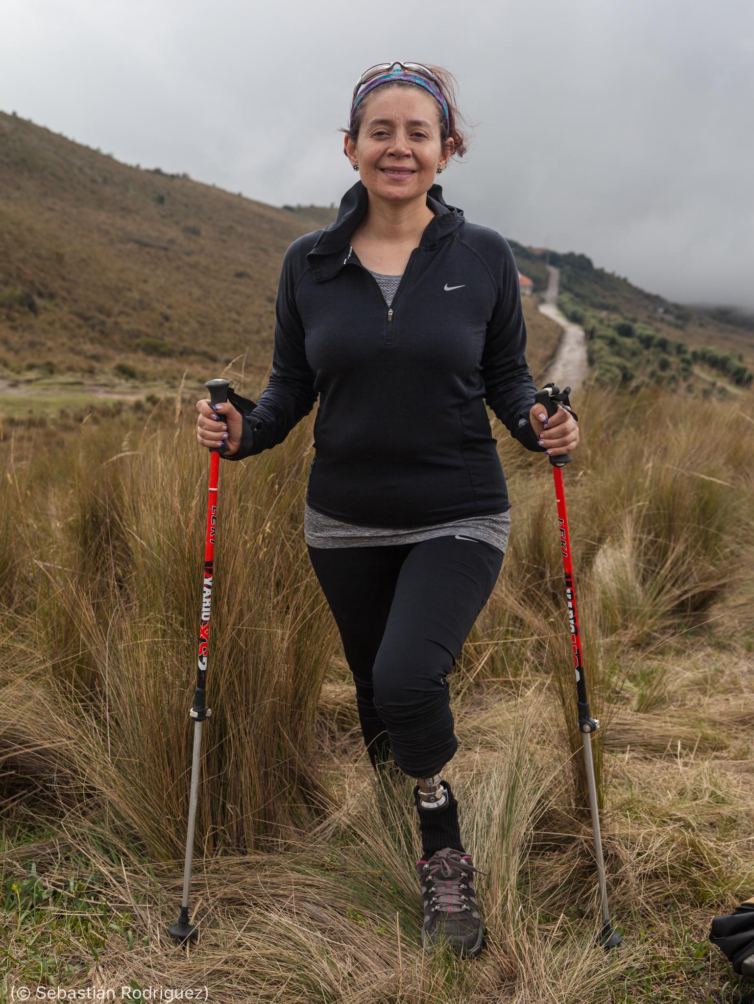 Wanita berjalan di lereng bukit dengan tongkat (© Sebastián Rodriguez)