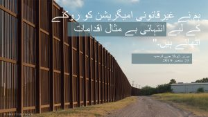 کچی سڑک کے ساتھ اُس بلند دیوار کی تصویر پر جس سے آر پار دیکھا جا سکتا ہے غیرقانونی امیگریشن کے بارے میں صدر ٹرمپ کا بیان۔ (State Dept.)