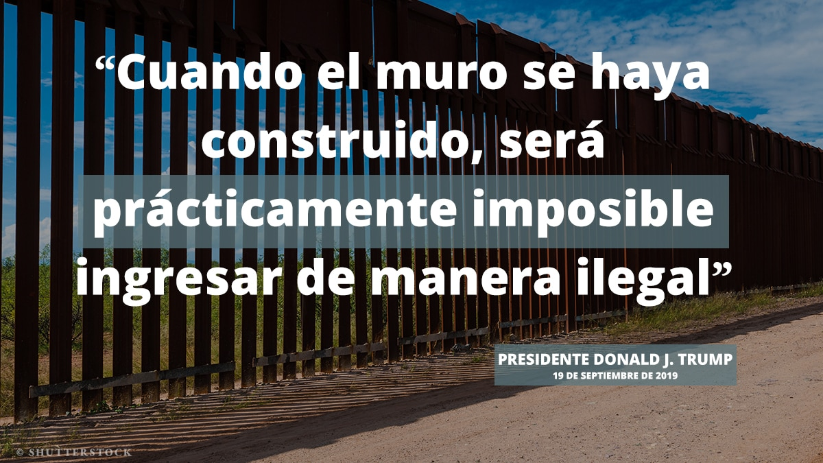 Muro alto, a través del cual se puede ver, ubicado a lo largo de un camino de tierra, con una cita superpuesta del presidente Trump sobre la construcción del muro (Depto. de Estado)