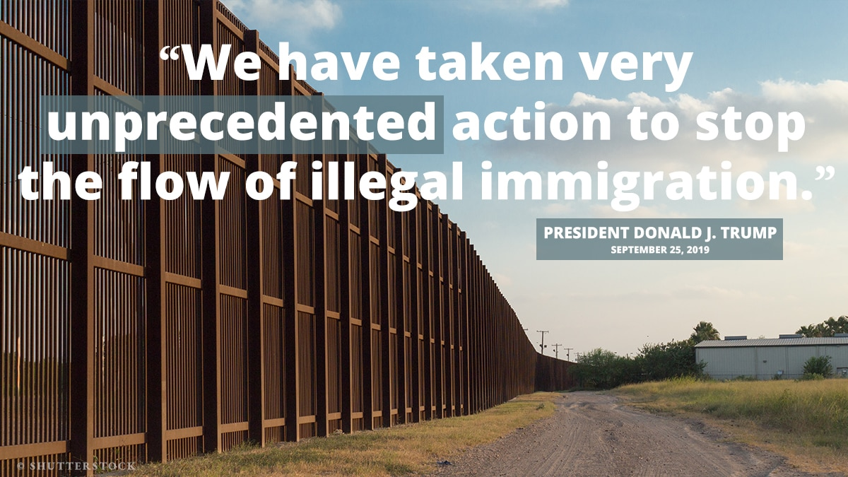 Tall, see-through wall along dirt road, with overlaid quote from President Trump on illegal immigration (State Dept.)