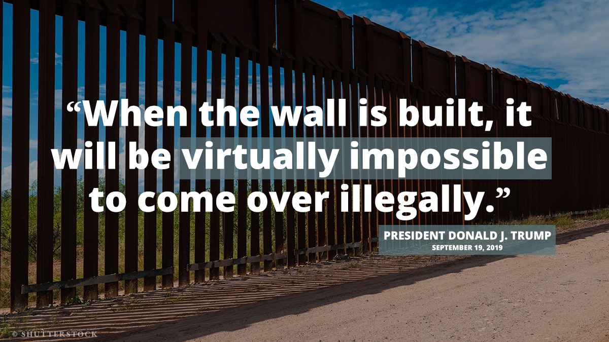Tall, see-through wall along dirt road, overlaid with quote from President Trump on wall construction (State Dept.)