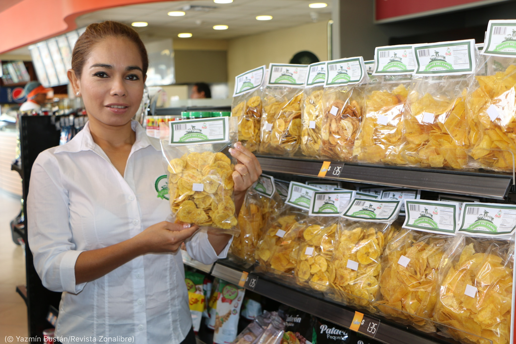 Woman holding bag of plantain chips and standing next to rack of chips in grocery store (© Yazmín Bustán/Revista Zonalibre)