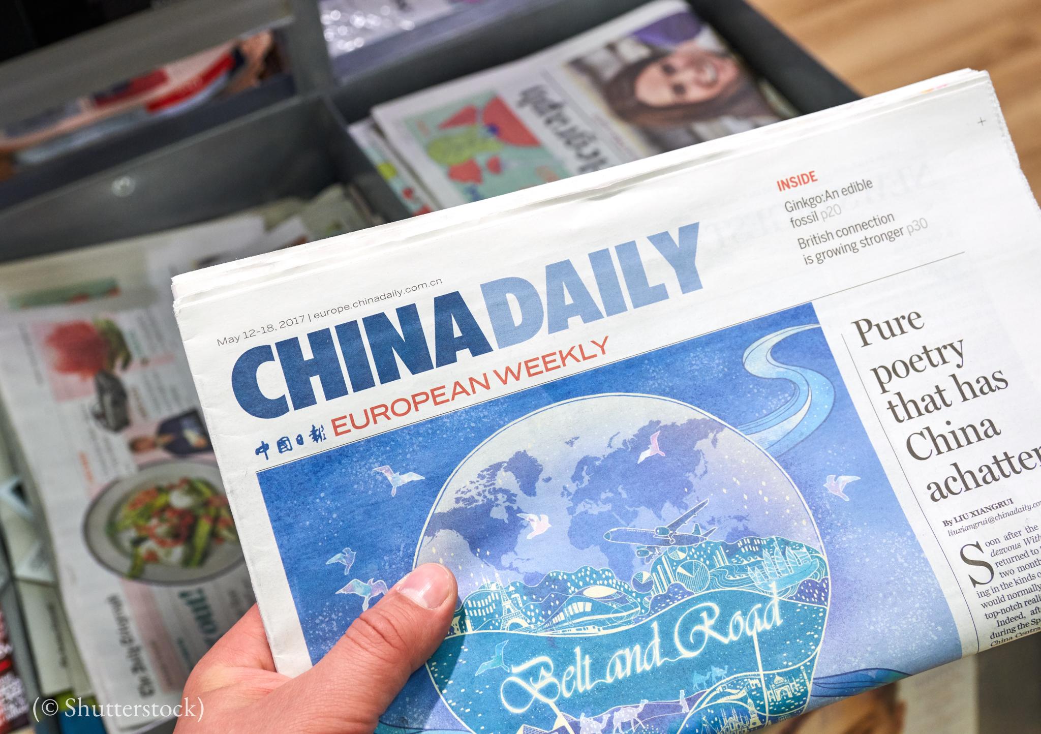 Hand holding folded newspaper (© Shutterstock)