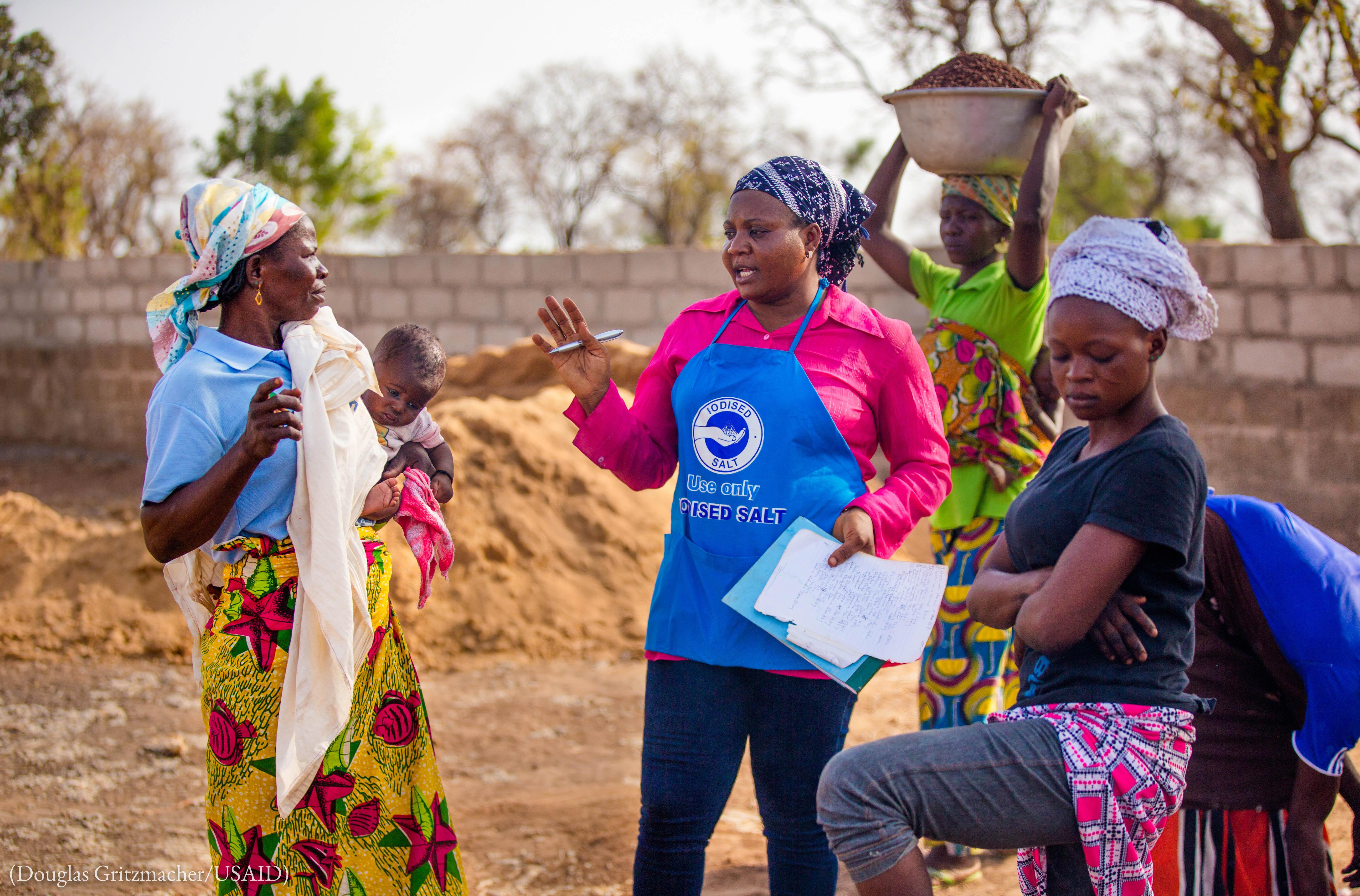 ایک عورت کام کرنے والی دوسری عورتوں سے محو گفتگو ہے۔ (Douglas Gritzmacher/USAID)