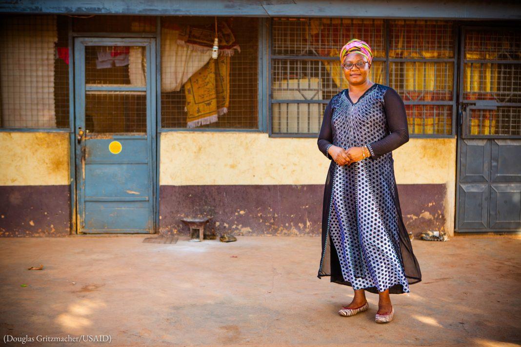 گھانا کی ایک عورت ایک عمارت کے باہر کھڑی ہے۔ (Douglas Gritzmacher/USAID)