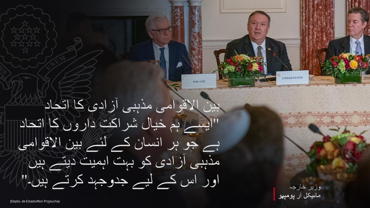 دیگر لوگوں کے ساتھ میز کے گرد بیٹھے وزیر خارجہ پومپیو کی تصویر پر بین الاقوامی مذہبی اتحاد کے بارے میں چسپاں تحریر۔ (State Dept./Ron Przysucha)