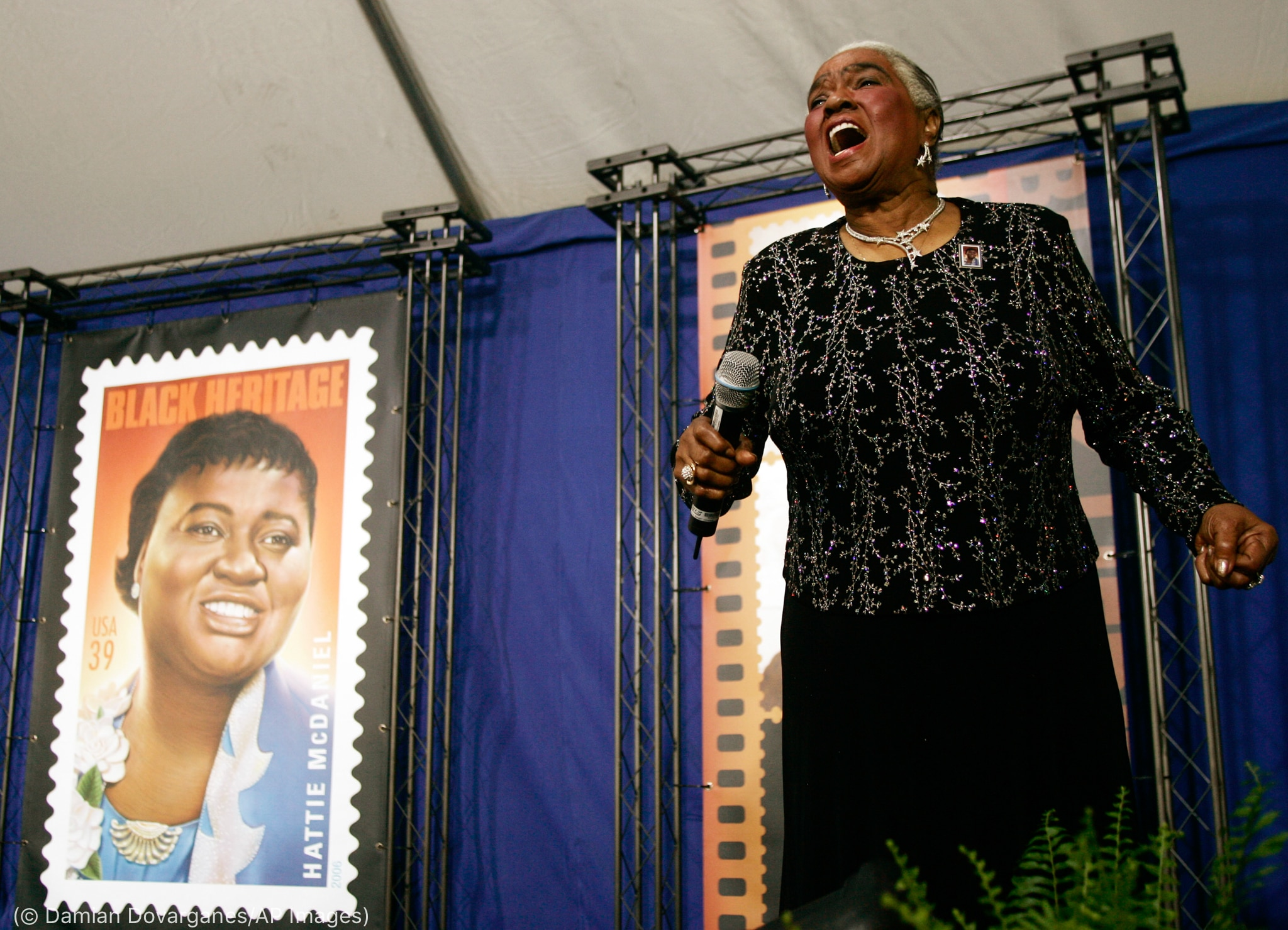 Linda Hopkins singing next to image of stamp (© Damian Dovarganes/AP Images)