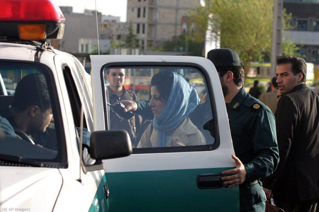 سر پر دوپٹہ لیے ایک عورت پولیس کی گاڑی کے قریب کھڑی ہے۔ (© AP Images)