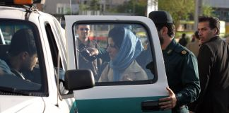 Woman wearing headscarf standing beside police vehicle (© AP Images)