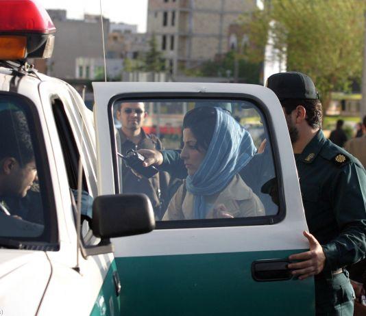 Una mujer con un velo en la cabeza de pie junto a un vehículo policial (© AP Images)
