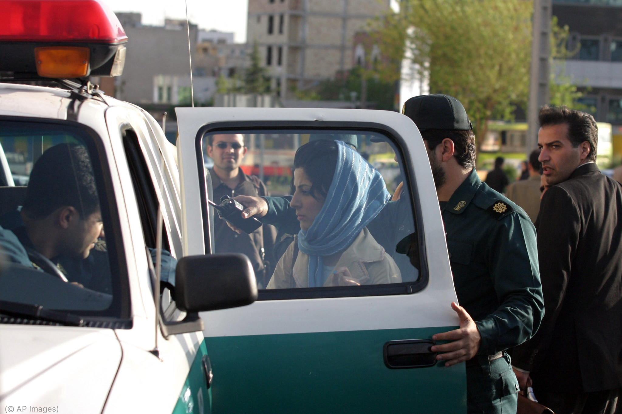 Woman wearing headscarf being put into police vehicle (© AP Images)