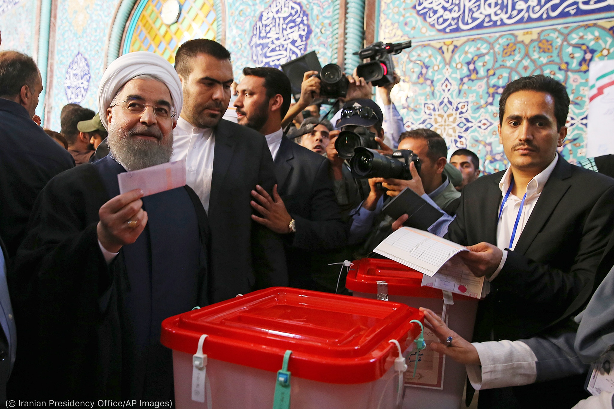 Rouhani holding ballot next to ballot box (© Iranian Presidency Office/AP Images)