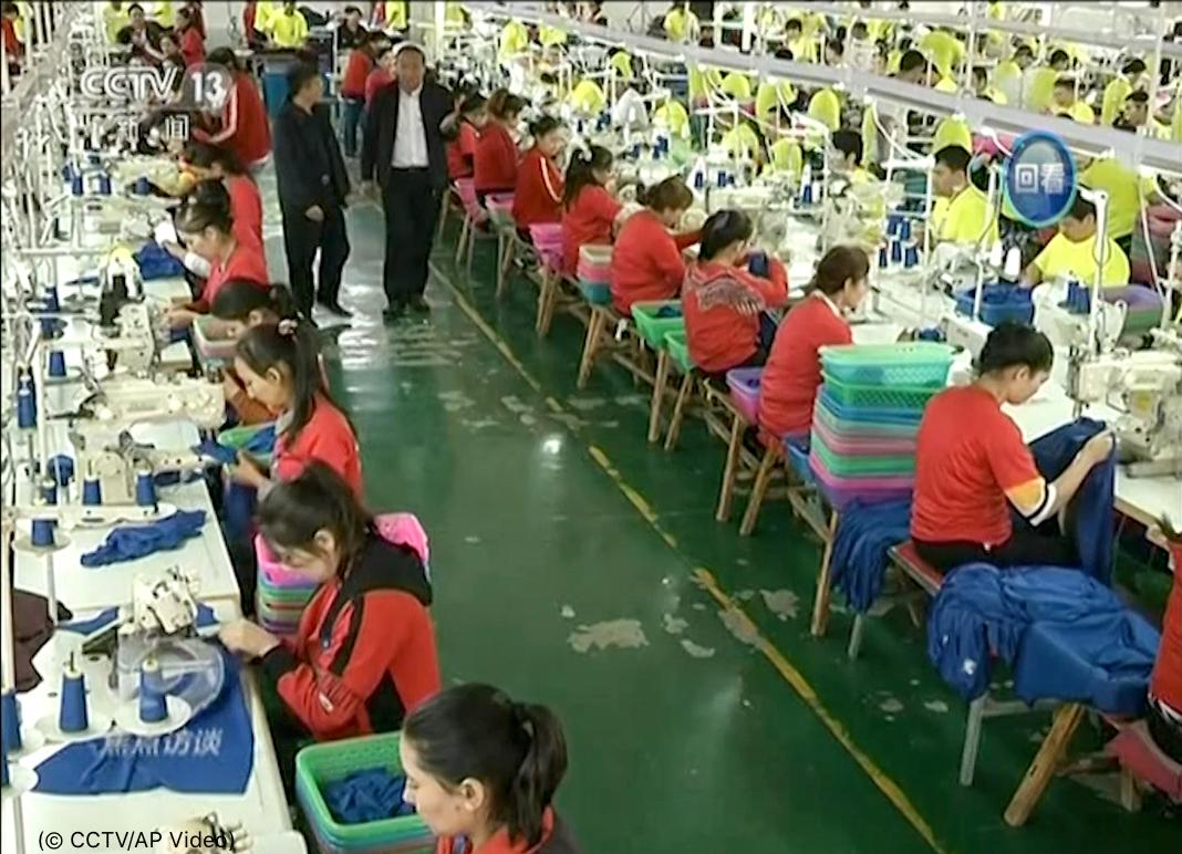 Pessoas trabalham sentadas em fileiras de mesas (© CCTV/AP Video)