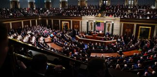 Large chamber with many people in seats facing person on dais giving speech (© Carolyn Kaster/AP Images)