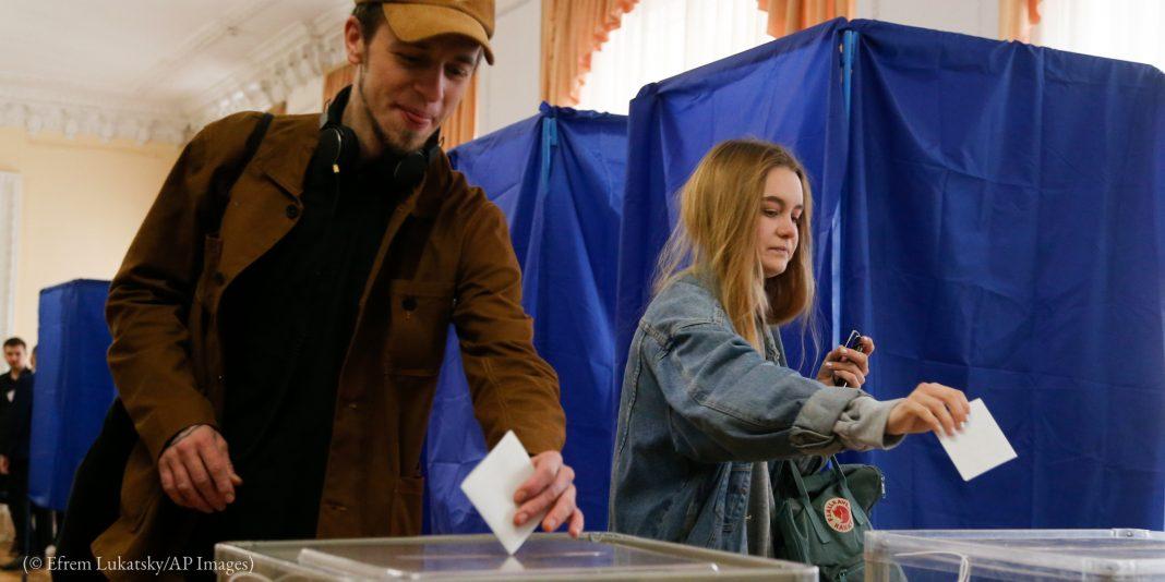 Duas pessoas inserem cédulas de papel em urnas (© Efrem Lukatsky/AP Images)