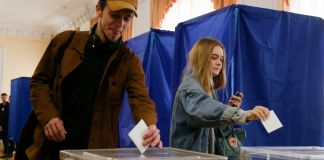 Two people putting paper ballots into ballot boxes (© Efrem Lukatsky/AP Images)