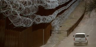 SUV traveling next to razor-wire-covered metal wall (© Charlie Riedel/AP Images)