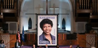 Enlarged version of stamp featuring portrait photo of woman on display in church (© Michael A. McCoy/AP Images)